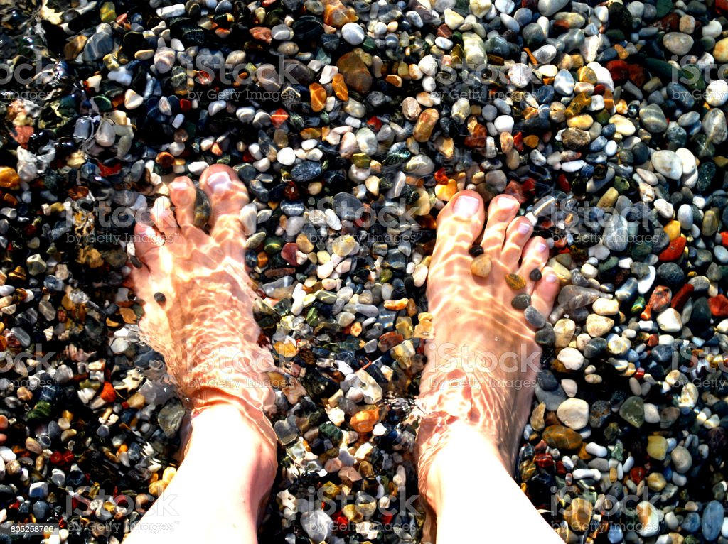Feet in Water Over Pebbles stock photo