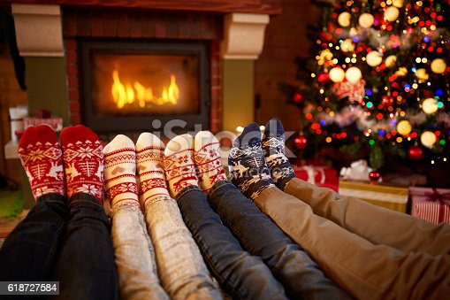 Feet in wool socks near fireplace in Christmas time concept