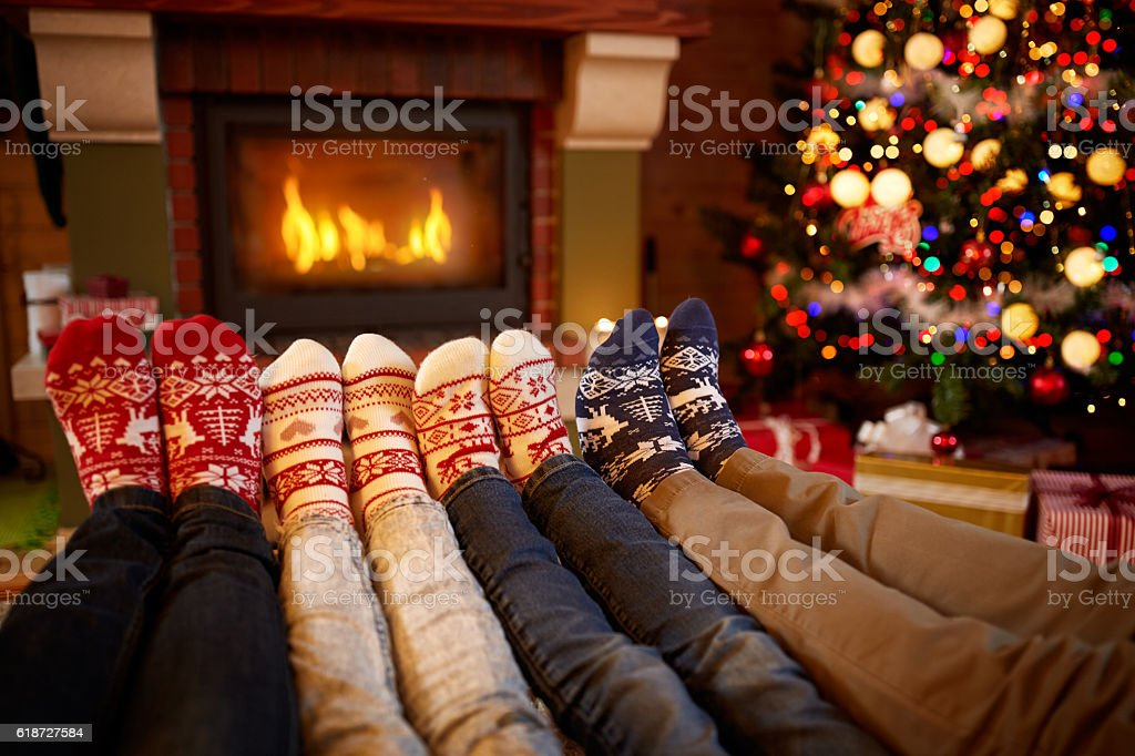 Feet in wool socks near fireplace in Christmas time stok fotoğrafı