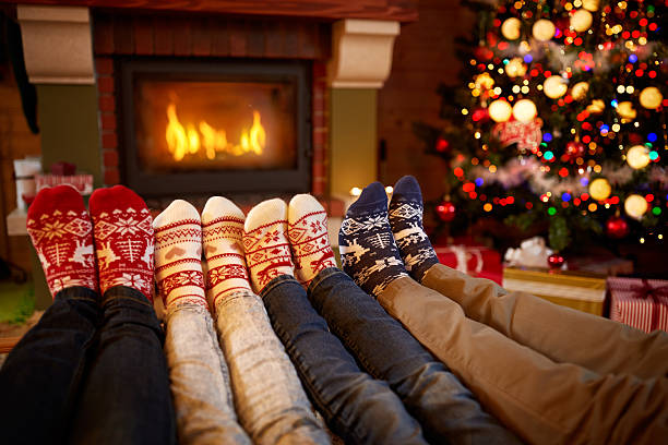 feet in wool socks near fireplace in christmas time - christmas families stock photos and pictures
