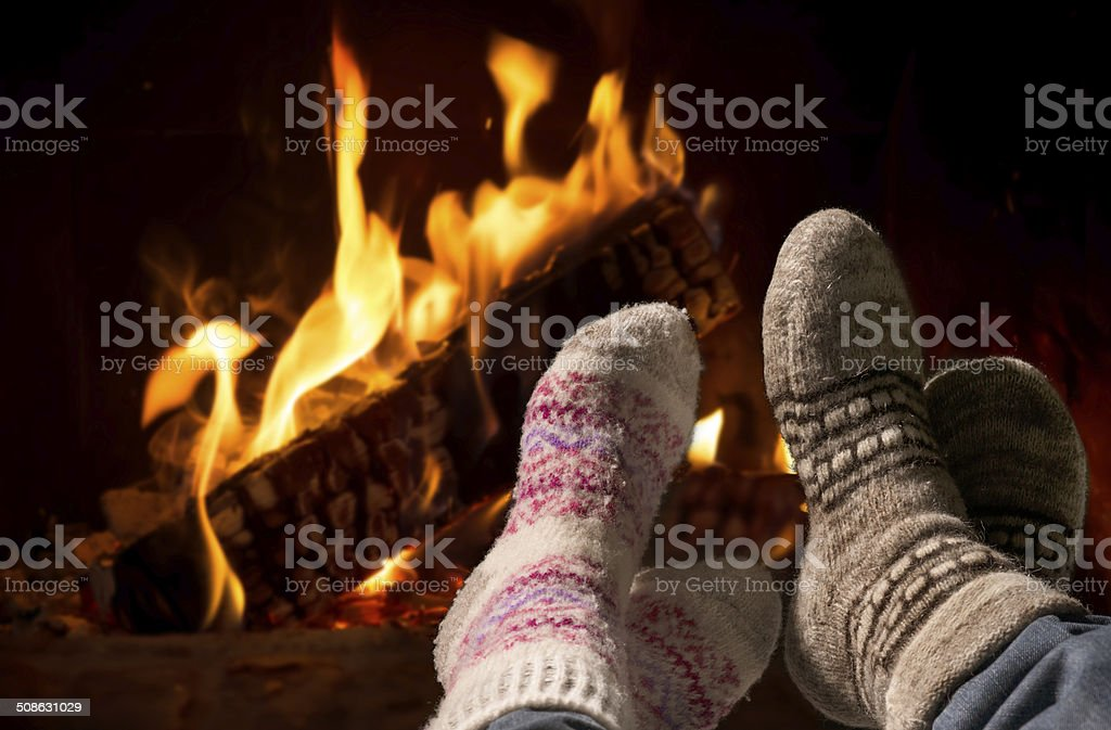 Feet in wool socks warming at the fireplace stock photo