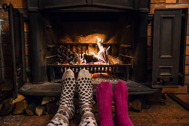 Feet in wool socks warming by cozy fire stock photo