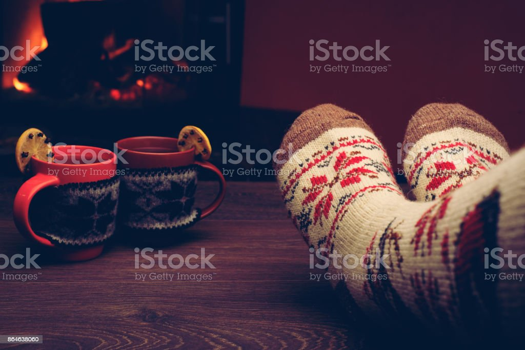 Feet in woollen socks by the Christmas fireplace. Woman relaxes by...