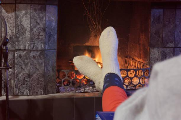 Feet in woollen socks by the fireplace stock photo