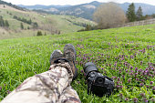 istock Feet legs and camera on green meadow with Carpathian mountains as a background. Bucovina, Romania 1316798068