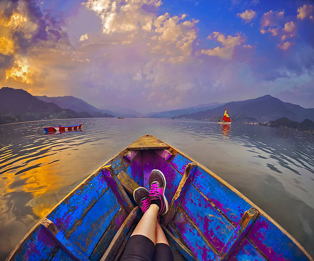 Feet luing in the boat ,landscape with  Himalaya clouds stock photo