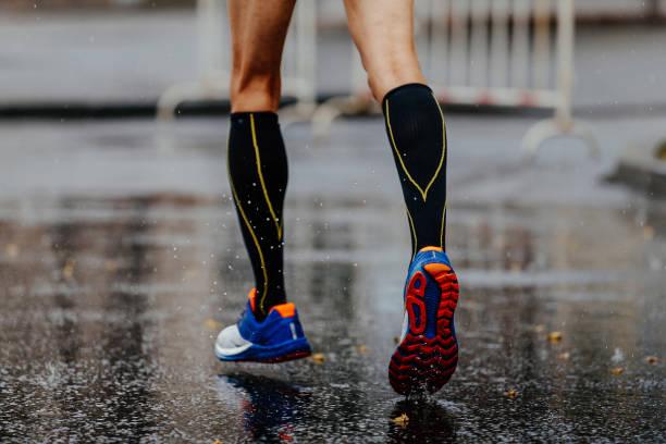 pies macho corredor en calcetines de compresión - foto de stock