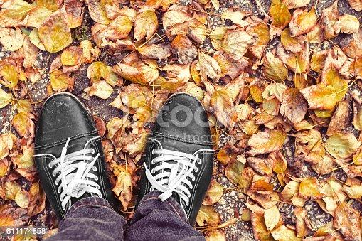 511983606 istock photo Feet Man walking on fall yellow leaves 611174858