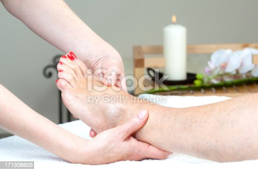 Applying foot massage in body care center