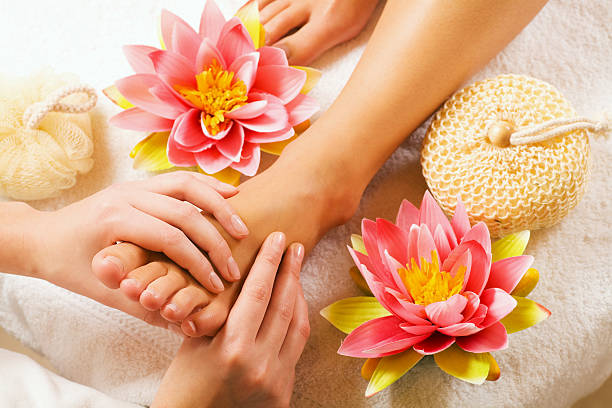 Feet massage Woman enjoying a feet massage in a spa setting (close up on feet) foot massage stock pictures, royalty-free photos & images