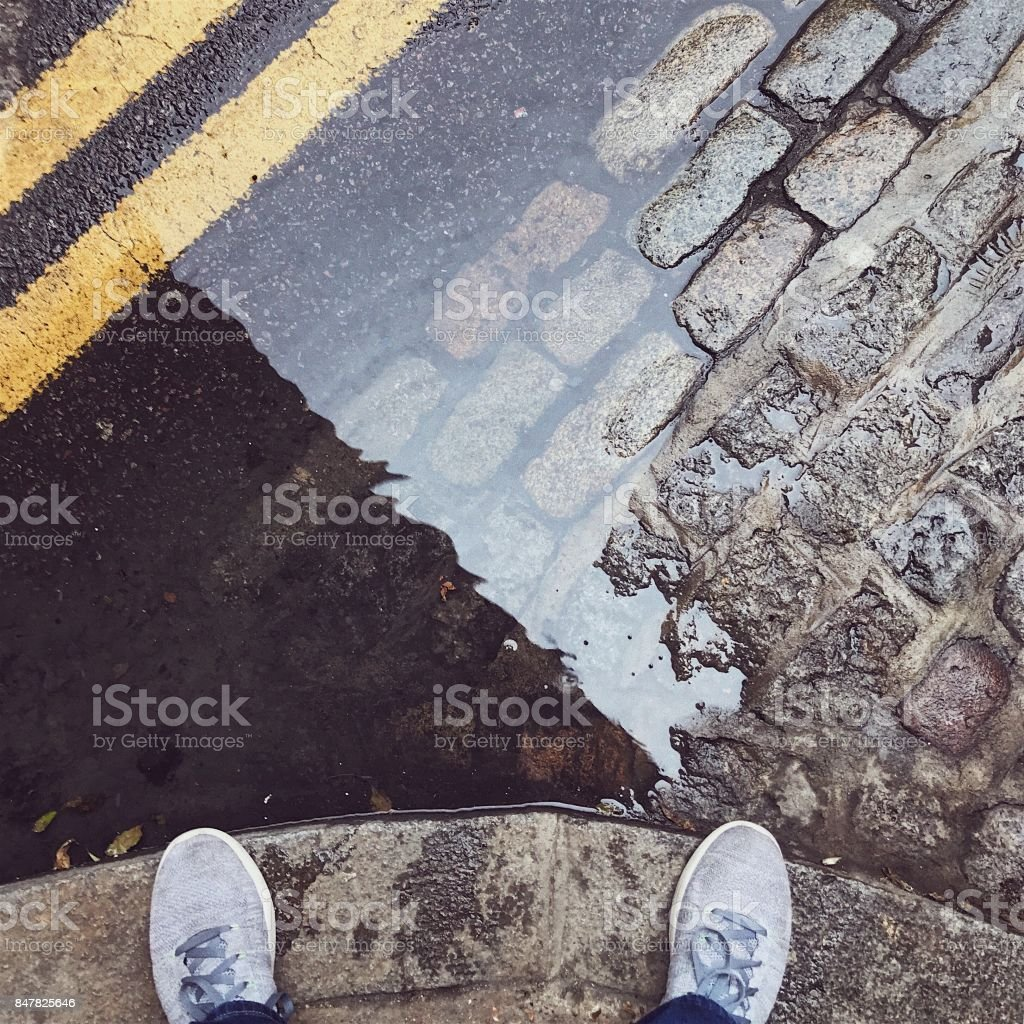 Feet next to a London puddle stock photo