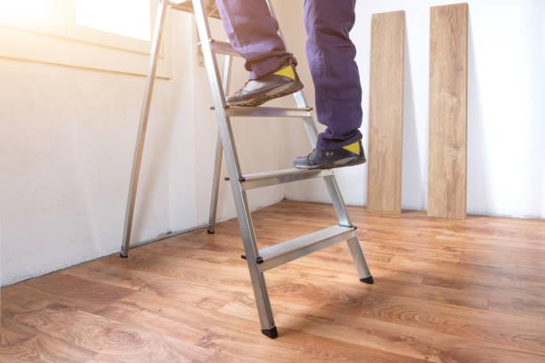 voeten van een timmerman klaar voor werk op een ladder - ladder stockfoto's en -beelden