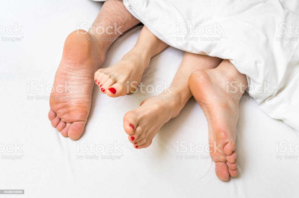Feet of a couple in bed under the blanket stock photo
