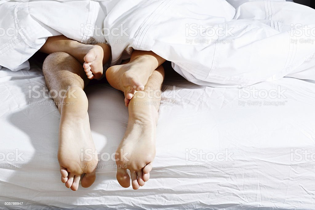 Feet of a couple making love are intertwined passionately stock photo