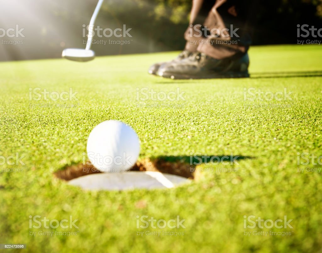 Feet of a golfer getting the ball in the hole
