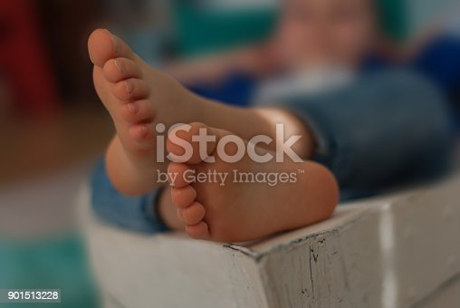 istock Feet of a little boy lying in a boat. Shallow depth of focus. 901513228