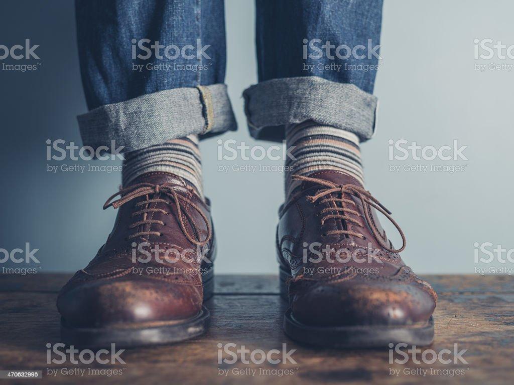 Feet of a man on wooden floor stock photo