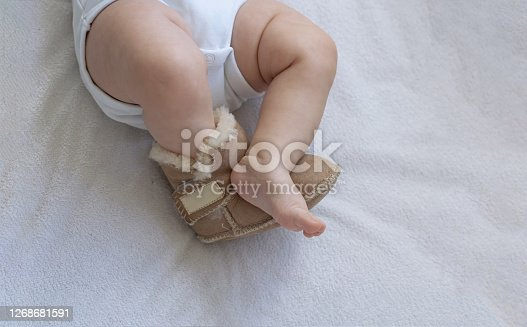 Feet of a newborn toddler close-up on the bed. On one foot boots made of leather and fur. The second foot is barefoot. Foot froze. Cropped vertically and horizontally.