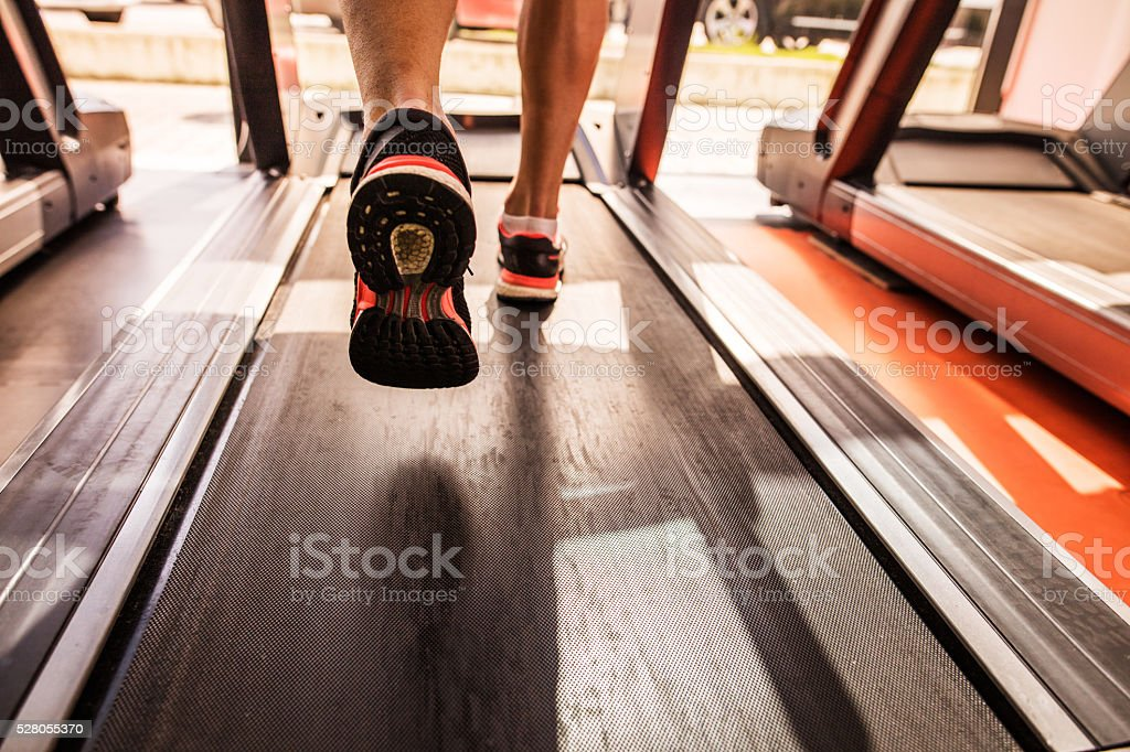 Feet of a runner on treadmill in a gym. stock photo