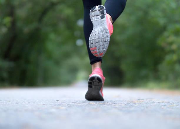 füße eines läufers. frau läuft im wald. nahaufnahme von sneakers. - joggerin stock-fotos und bilder