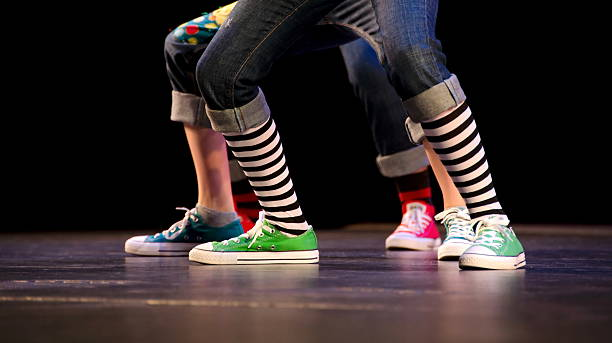 Feet of a trio of hip-hop performer in colorful sneakers stock photo