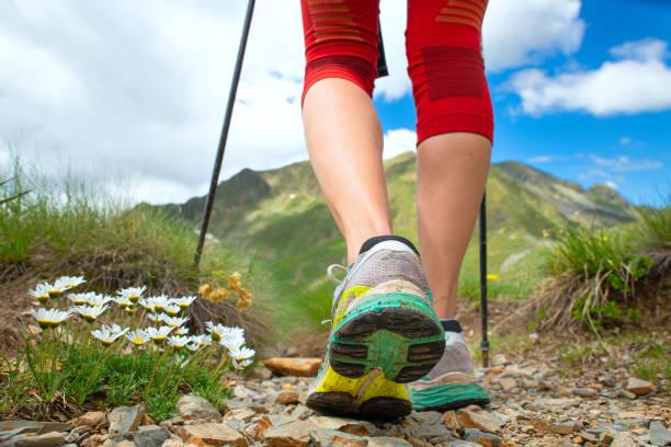 Füße einer Frau, die Wanderungen in den Bergen mit nordic-Walking-Stöcke – Foto