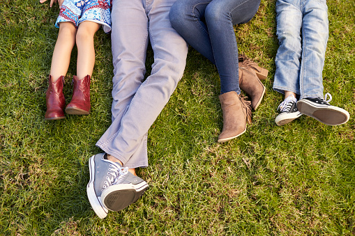 istock Feet of a young family lying on grass in a park, crop 620382830