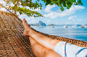 Feet of adult woman relaxing in a hammock on the beach during summer holiday in El nido, Palawan, Philippines.