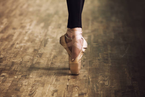 feet of ballerina in training shoes on the parquet wooden floor close up retro style - dance class stock photos and pictures