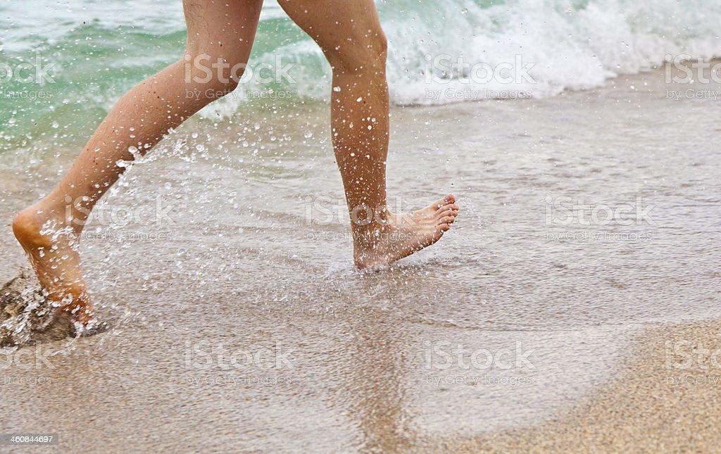 feet of boy running along the beach royalty-free stock photo