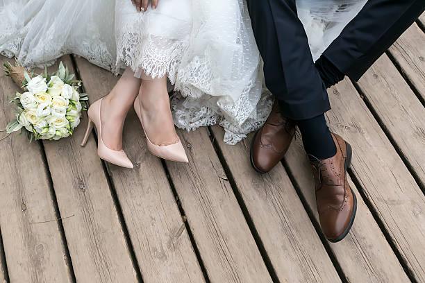 füße von braut und bräutigam, hochzeit schuhe (weicher fokus). - brautstrauß aus holz stock-fotos und bilder