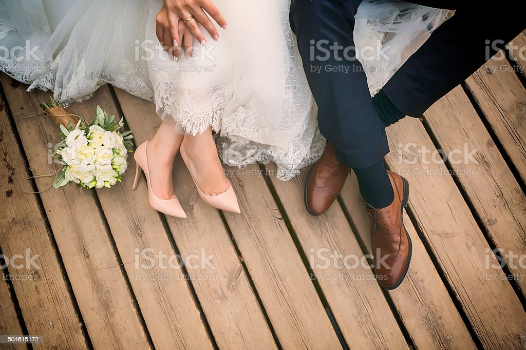 feet of bride and groom, wedding shoes . Cross processed image for...