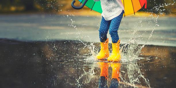 stopy dziecka w żółtych gumowych butach przeskakujących przez kałużę w deszczu - deszcz zdjęcia i obrazy z banku zdjęć