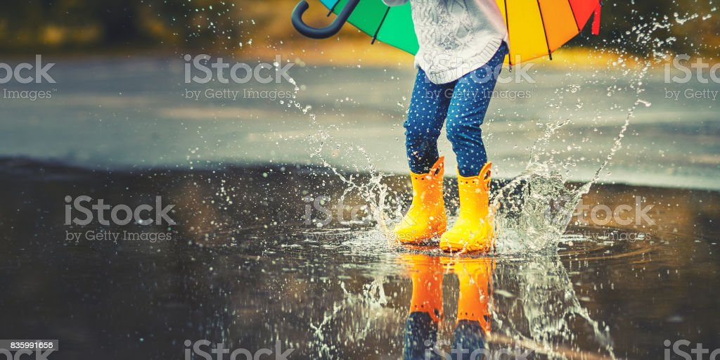 Feet of  child in yellow rubber boots jumping over  puddle in rain stock photo