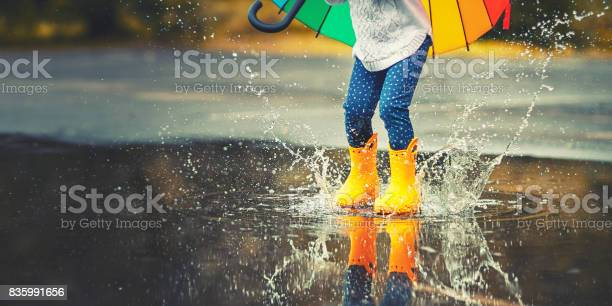 Feet of child in yellow rubber boots jumping over a puddle in the rain