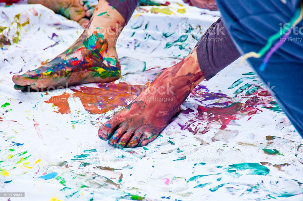 feet of children full of colorful gouache stock photo