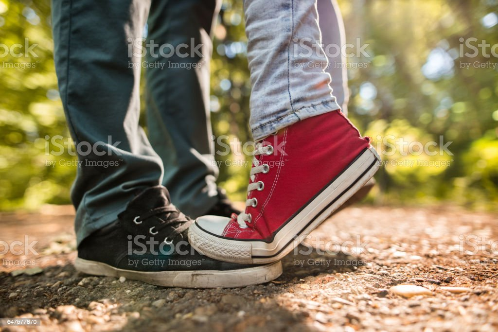 569175fd2 Feet of couple in love standing on footpath in nature. royalty-free stock  photo