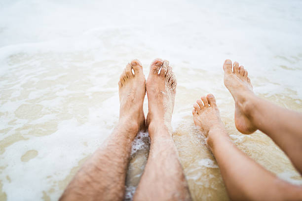 feet of couple playing on the beach - woman leg beach pov stock photos and pictures