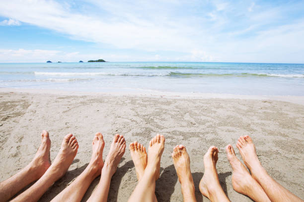 feet of family or group of friends together on beach stock photo