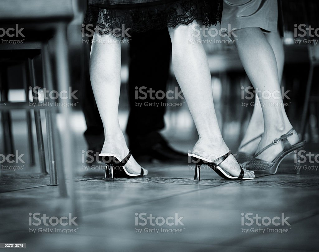 Feet of female wedding guests in heel shoes in party stock photo