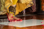 istock Feet Of Indian Classical Girl Kathak Dancer In Traditional Dress Or Costume And Ghungroo Ghungru Or Noopura Musical Anklet With Red Dye Altha Alah Mahavar Or Alta Performing Dance Mudras On Stage Show 1305862517