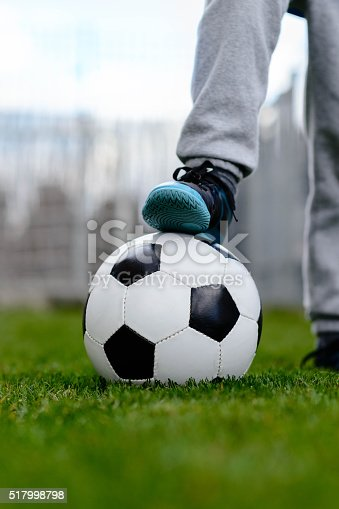 621475196 istock photo Feet of little boy on ball on football field 517998798