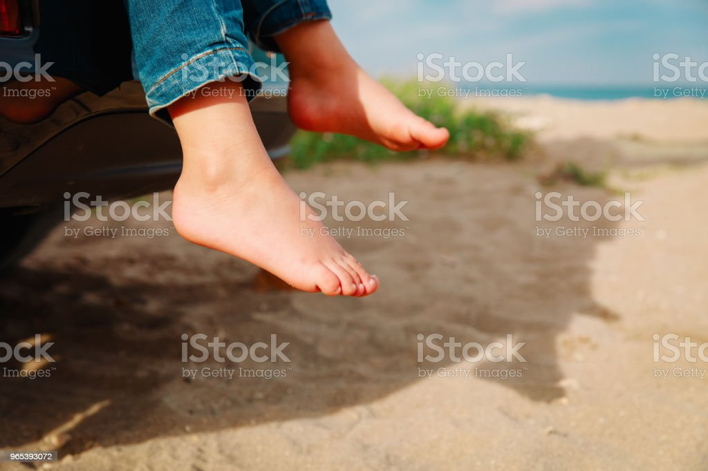feet of little girl travel by car on beach royalty-free stock photo