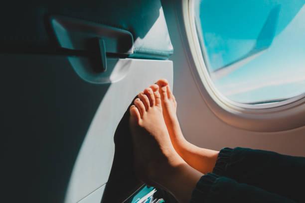 Füße des kleinen Mädchens reisen mit dem Flugzeug, Kind im Flug, Sicherheit – Foto