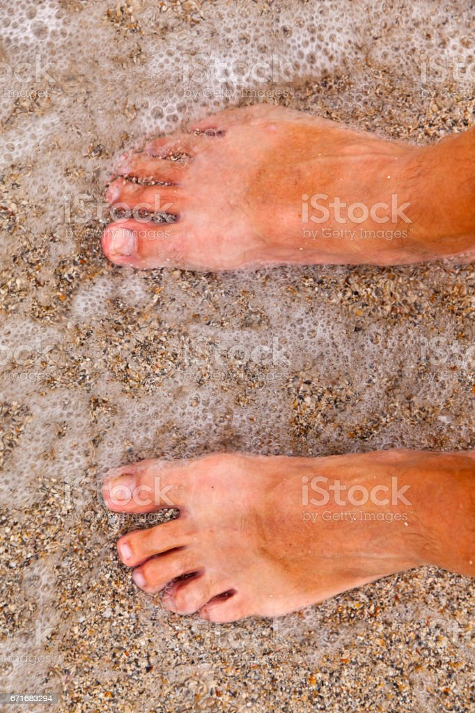 feet of man at the beach stock photo