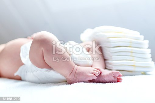 istock Feet of newborn baby on changing table with diapers 641681210