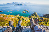 feet of people hikers relaxing on top of the mountain, travel background, hiking shoes