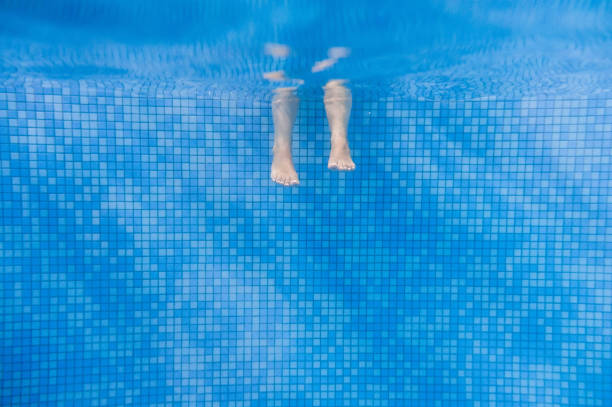 Feet of people moving under the water in the pool. Children legs. Summer. Funny underwater legs in swimming pool, under water view of women or kids, vacation and sport concept.