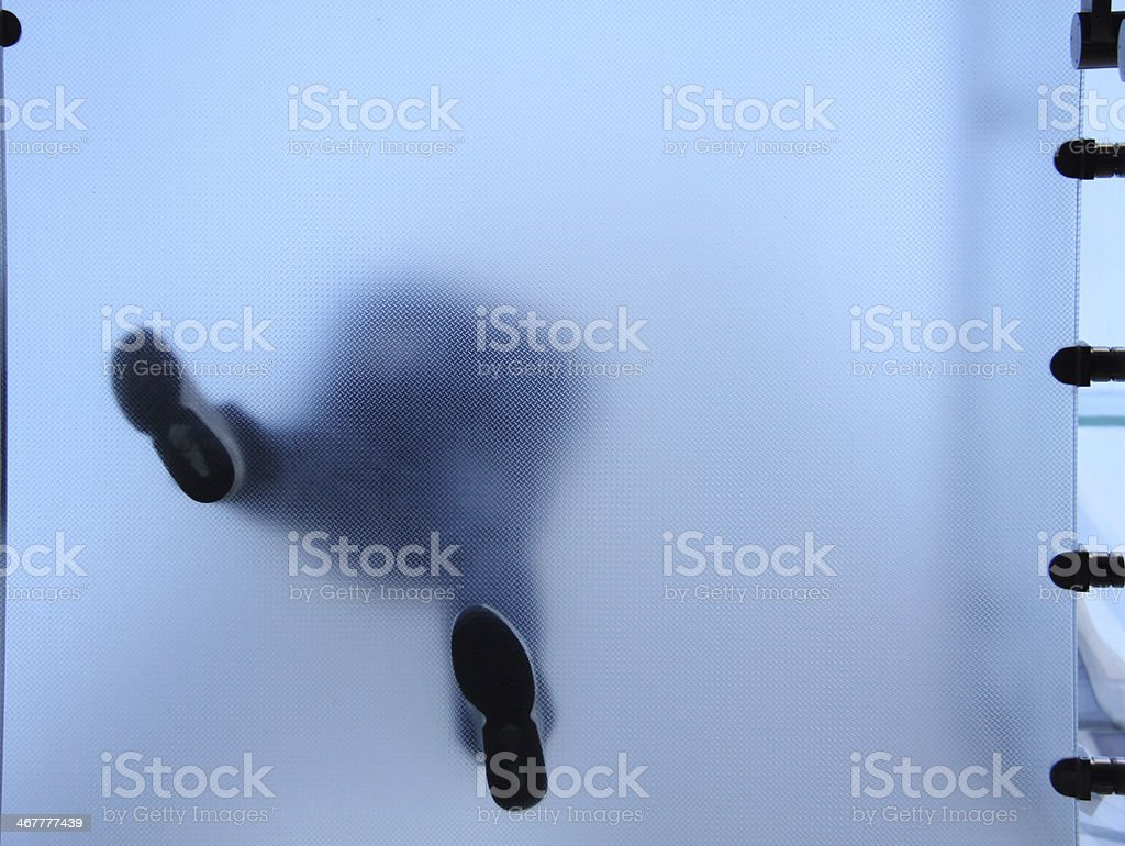 Feet of people who standing on translucent glass stock photo