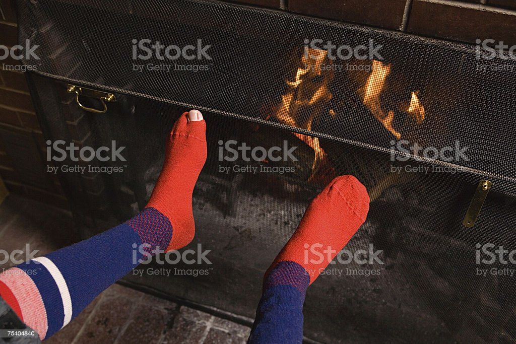 Feet of person by fire stock photo